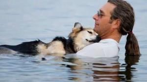 man-ligt-uren-met-zijn-hond-in-het-water-om-hem-te-laten-ontspannen